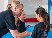 two young martial artist girls being helped by instructor